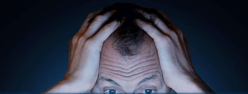 a man holds his head in frustration